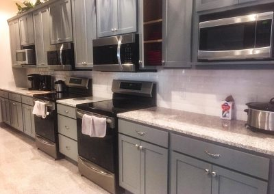 Gray kitchen cabinets with custom natural stone granite countertops by Gordon Creek Granite of Hicksville, Ohio.