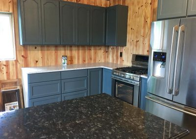 Gray kitchen cabinets with custom natural stone granite countertop by Gordon Creek Granite of Hicksville, Ohio.