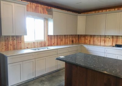 White kitchen cabinets with custom natural stone countertops by Gordon Creek Granite of Hicksville, Ohio.