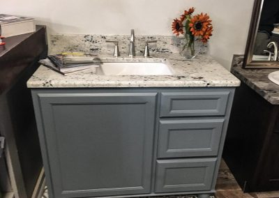 Gray vanity cabinet with custom natural stone granite countertop by Gordon Creek Granite of Hicksville, Ohio.