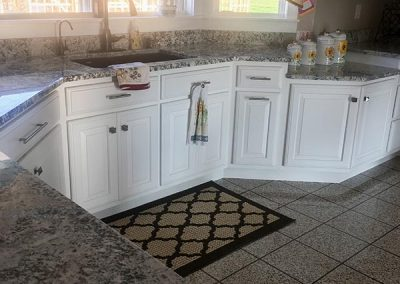 White kitchen cabinets with custom natural stone granite countertop by Gordon Creek Granite of Hicksville, Ohio.